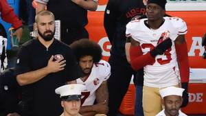 San Francisco 49ers quarterback Colin Kaepernick i midten protesterer ved at sætte sig på knæ under den amerikanske nationalsang for at demonstrere sin utilfredshed med racemæssig ulighed i samfundet og politivold over for sorte i USA. Foto: AP