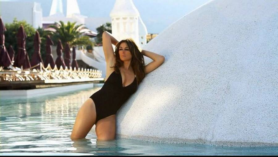 Hurley posrer her i en sort enkelt badedragt.(Foto: Liz Hurley 2013 Beach Collection)