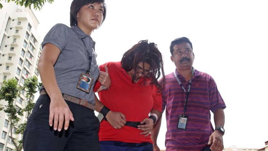Den dræbte barnepiges arbejdsgiver på vej i retten i Singapore. Hun blev fundet skyldig i alle 28 kriminelle forhold. Foto: Ritzau Scanpix