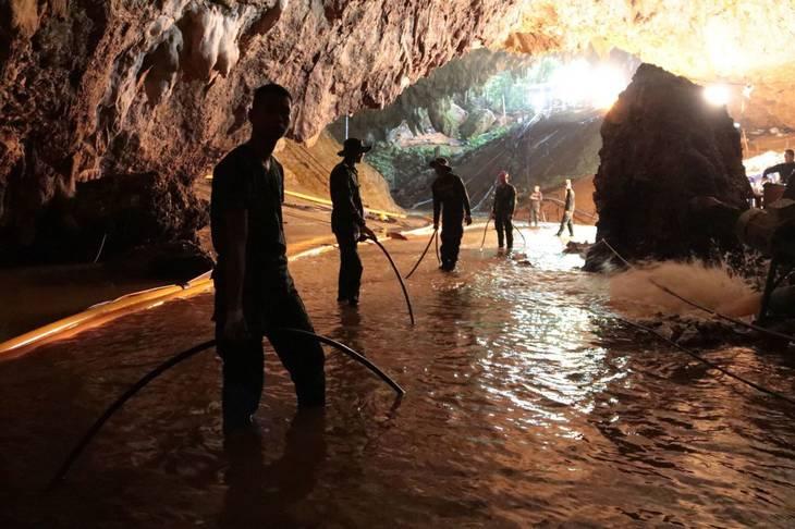 Thailandske redningsarbejdere står ved indgangen til Tham Luan Nang Non-grotten, hvor de forsøger at pumpe vandet væk fra den 10 kilometer lange grotte, hvor 12 drenge og deres fodboldtræner var fanget i 18 dage. Foto: Royal Thai Navy/AP