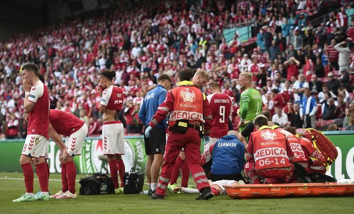 Sundhedspersonale arbejder med liggende Christan Eriksen, og alt står i de minutter stille i Fodbold-Danmark. Foto: Lars Poulsen