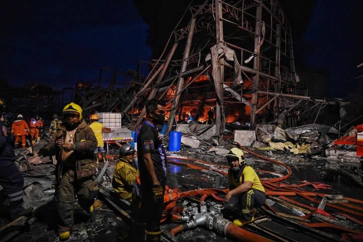 Brandmænd arbejder på stedet, efter en stor eksplosion mandag nat lagde en fabrik i ruiner. Foto: Lillian Suwanrumpha / Ritzau Scanpix