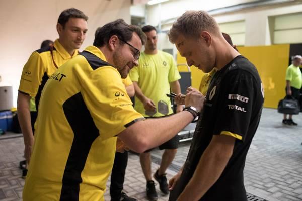 Renault-mekanikerne i færd med at skrive på deres snart tidligere kollega. Foto: Jan Sommer