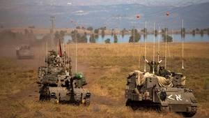 Israelske soldater kører i pansrede mandskabsvogne ved Golanhøjderne. Foto: AP