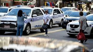Billedet af disse to asiatiske kvinder, der tager  turistbilleder i forbindelse med en døds-katastrofe i Melbourne er nu gået verden rundt. (Foto:AFP)